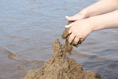 The hand of the child builds a sand castle on the beach on the b. Ackground of water summer day stock photos
