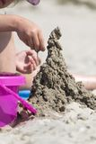 Child`s hand builds a sand castle. The hand of the child creates a sand castle royalty free stock photography