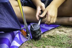 Hand of a child holding a rubber hammer Hammered steel mounting tent down on the ground.  royalty free stock photo