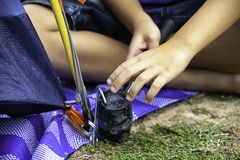 Hand of a child holding a rubber hammer Hammered steel mounting tent down on the ground.  stock image