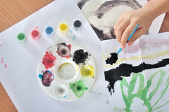 Hand of child painting with brush and color Royalty Free Stock Images