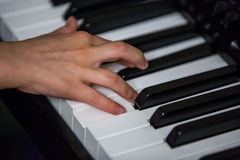 Hand of child playing piano close up. The hand of child playing piano close up Stock Photos