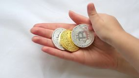 The hand of the child puts a coin bitcoin in the hand of a young woman, and then takes it - 2. Crypto currency in the. Hands of women and children in slow stock video