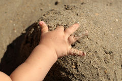 Hand of child on sand Stock Photos