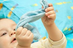 The hand of the child and sock. The child lay and examines a blue sock royalty free stock photo