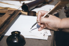 Hand of a child writing with a feather pen, Trentino Alto Adige, Italy. Royalty Free Stock Photos