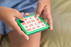 Hand of children playing number slider puzzle Royalty Free Stock Photos