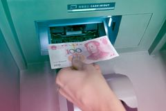 Hand with Chinese RMB placed money in ATM. Keep it in a saving  bank account Royalty Free Stock Photo