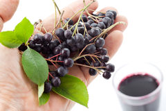 Hand with chokberries, glass with aronia juice Royalty Free Stock Photo