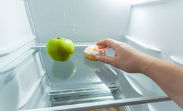 Hand choosing donut instead of apple lying in fridge Stock Photography