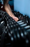 Hand choosing a dumbbell. Hand of a man choosing a dumbbell out of set of black weights Royalty Free Stock Photo