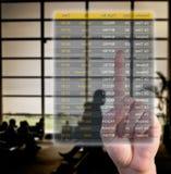 Hand choosing flights pushing a screen interface. At the airport Royalty Free Stock Image