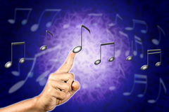 Hand choosing a music note. Royalty Free Stock Photos