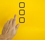 Hand choosing option. Hand choosing one check box option on yellow background Stock Photography