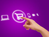 Hand choosing shopping cart symbol. From media icons on purple Royalty Free Stock Image