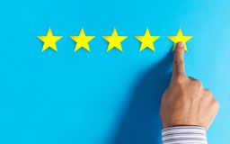 Hand choosing 5 stars rating on blue background stock images