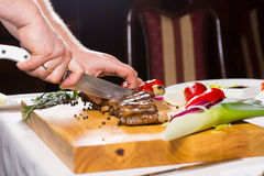Hand Chopping Meat With Knife On Cutting Board Stock Photo
