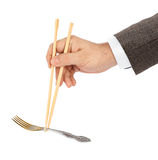 Hand with chopsticks and fork Royalty Free Stock Image