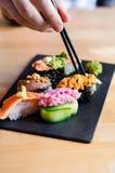 Eating nigiri sushi. Hand with chopsticks grabbing nigiri sushi royalty free stock images