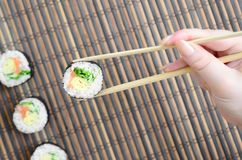 A hand with chopsticks holds a sushi roll on a bamboo straw serwing mat background. Traditional Asian food.  royalty free stock photo