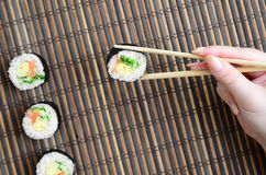 A hand with chopsticks holds a sushi roll on a bamboo straw serwing mat background. Traditional Asian food.  royalty free stock image