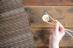 A hand with chopsticks holds a sushi roll on a bamboo straw serwing mat background. Traditional Asian food.  stock photo