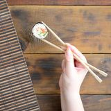 A hand with chopsticks holds a sushi roll on a bamboo straw serwing mat background. Traditional Asian food.  stock image