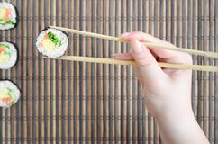 A hand with chopsticks holds a sushi roll on a bamboo straw serwing mat background. Traditional Asian food.  stock photos