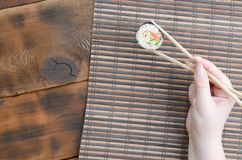 A hand with chopsticks holds a sushi roll on a bamboo straw serwing mat background. Traditional Asian food.  stock photography