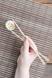 A hand with chopsticks holds a sushi roll on a bamboo straw serwing mat background. Traditional Asian food.  royalty free stock photos