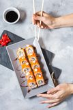 Hand with chopsticks on sushi set with soy sauce on concrete table. Top view stock photography