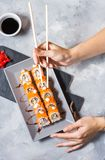 Hand with chopsticks on sushi set with soy sauce on concrete table. Top view stock photos