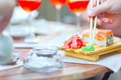 Hand with chopsticks and wasabi sushi close ginger Stock Images