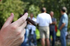 Hand with cigar and many people in the background out of focus Royalty Free Stock Images