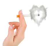 Hand with cigarette and heart shaped smoke. Isolated on white background Stock Image