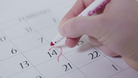 Hand circles 14th February in the calendar in slow motion stock footage