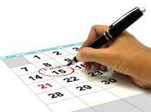 Hand Circling Tax Date on a Calender with Pen. Circling Tax Date on a Calender with Pen Royalty Free Stock Photos