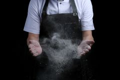 Hand clap of chef with flour on black background isolated royalty free stock photo
