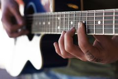 Hand of classical guitar player with fingers at the strings and the neck of the guitar. Photo of hands of classical guitar player with tatoo. One hand with stock images