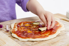 Hand of cld making fresh pizza Stock Photography