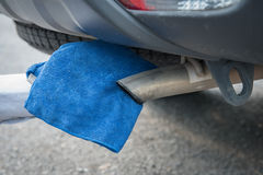 Hand cleaning the car exhaust pipe. With microfiber cloth Stock Photo