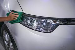 Hand cleaning car headlight on a white car royalty free stock photos
