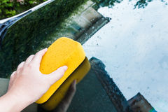 Hand cleaning car's window with sponge. Stock Photos