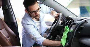 Hand cleaning car steering wheel with microfiber cloth. Cleaning car steering wheel with microfiber cloth Royalty Free Stock Photo