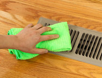 Hand Cleaning Grill Plate of Floor Heating Vent in Home royalty free stock photography