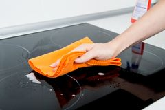 Hand cleaning induction stove stock photography