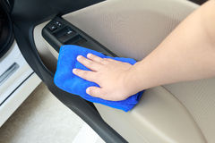 Hand cleaning interior car door panel with microfiber cloth Royalty Free Stock Photography