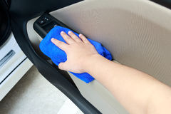 Hand cleaning interior car door panel with microfiber cloth Stock Images