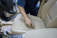 Hand cleaning the leather car seat Stock Photography