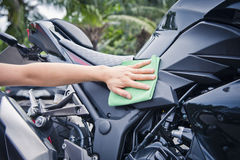Hand with cleaning motorcycle Royalty Free Stock Image